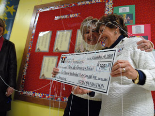 Two ladies hug each other and celebrate as a scholarship check is presented