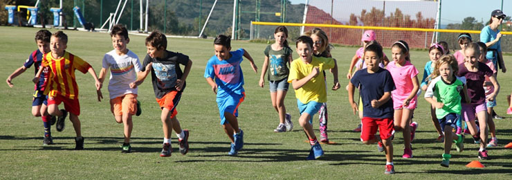 Students run across the field in a relay race.