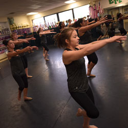 dance students reaching their arms out during excercise