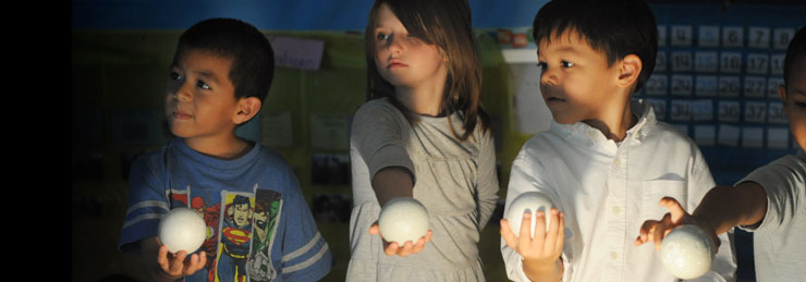 3 children hold onto a ball like object as they listen for instructions