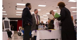 Photo of the KISD Job Fair inside of an auditorium, potential employees visiting with hiring staff.