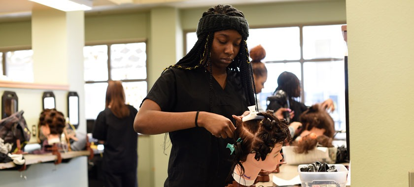 Cosmetology students practice on their hair coloring skills