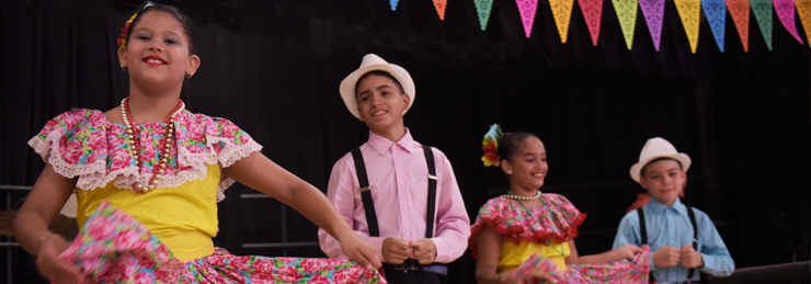 Children dressed in folkloric outfits participating in a school activity during Hispanic Heritage month.