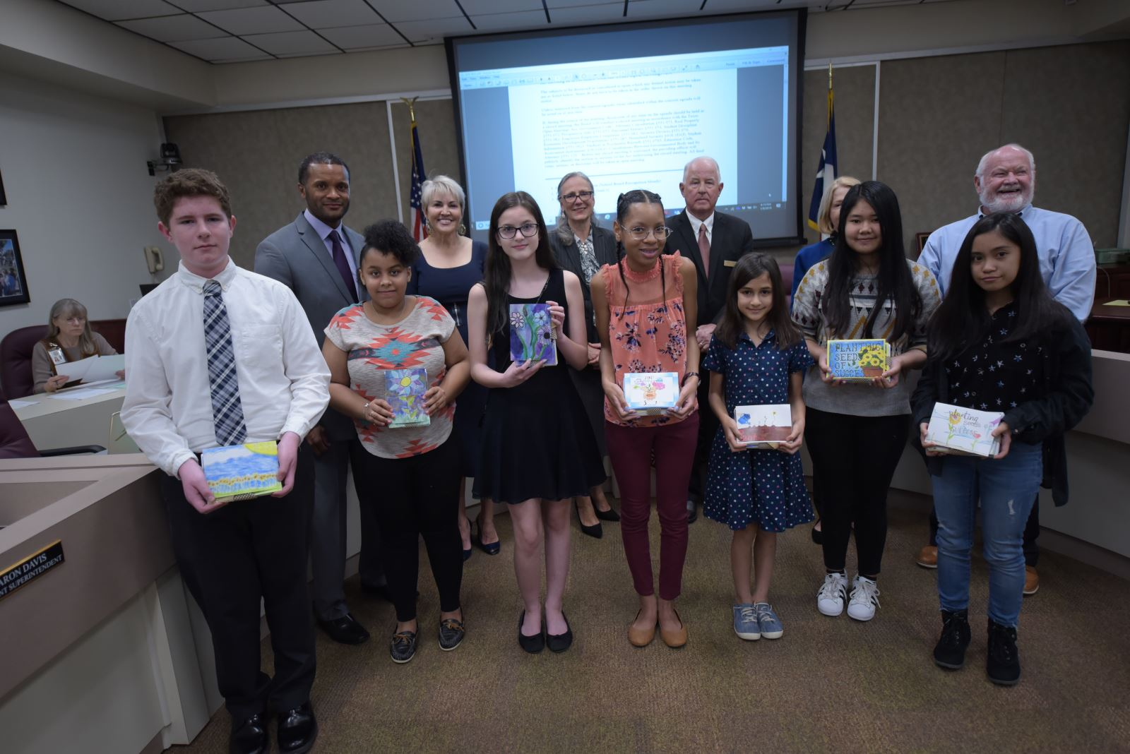 Students presenting the school board their award winning card designs.