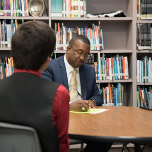 The interviewer takes notes during the student's interview.